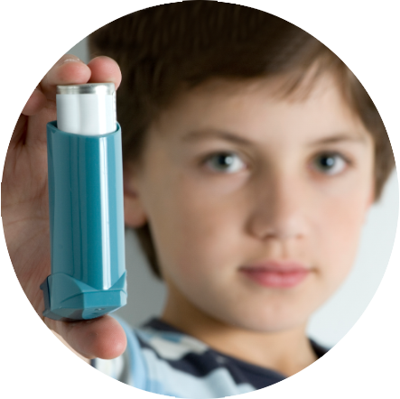 Boy holding an inhaler used for treating his asthma